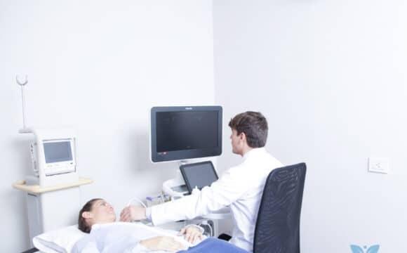 Médico e paciente durante exame de ecodoppler