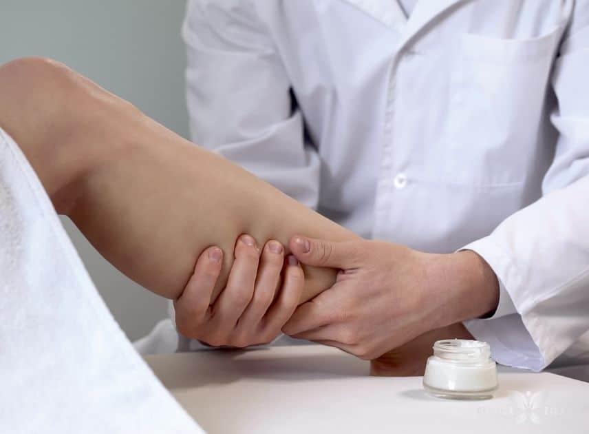 Médico enquanto examina perna de paciente